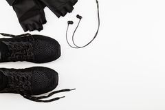 Черные ботинки, перчатка и наушники спорта на белой предпосылке стоковая фотография
