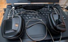Черные большие наушники dj вышли на компьтер-книжку после смешивая музыки Стоковые Фото