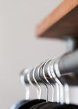Черные вешалки повиснули на деревенском списке избирателей под полкой в шкафе Стоковые Фото