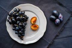 Черные виноградины и сливы на плите Стоковые Фотографии RF