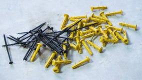 Черные винты металла лежа рядом с желтыми пластиковыми шпонками на грубой поверхности стоковое изображение