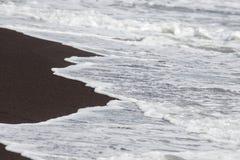 Черные вулканические песок и волны на пляже в Legazpi, Филиппинах стоковые изображения