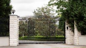 Черные въездные ворота подъездной дороги металла установленные в загородку Стоковая Фотография RF
