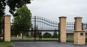 Черные въездные ворота подъездной дороги металла установленные в загородку Стоковые Изображения RF