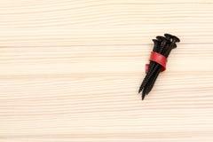 Черные длинные винты связанные с красной пластиковой ложью прокладки на деревянной поверхности стоковая фотография rf