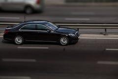 Черные езды Мерседес на дороге Против предпосылки запачканных деревьев стоковая фотография rf
