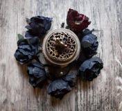 Черные искусственные цветки с горелкой ладана Стоковые Изображения RF