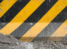 Черные и желтые нашивки на строительной площадке конкретной поверхности Стоковое Изображение