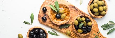 Черные и зеленые оливки на белизне Стоковое Фото