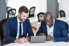 Черные и кавказские бизнесмены смотря портативный компьютер Стоковые Изображения