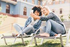 Черные и кавказские девушки на кушетках outdoors принимая selfie Стоковые Изображения