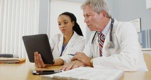 Черные и кавказские доктора работая на таблетке в офисе Стоковая Фотография