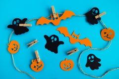 Черные и оранжевые бумажные украшения - призраки, тыквы и летучие мыши на веревочке с штырями на голубой предпосылке, взгляд свер стоковые изображения