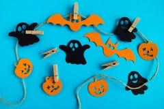 Черные и оранжевые бумажные украшения - призраки, тыквы и летучие мыши на веревочке с штырями на голубой предпосылке, взгляд свер стоковые фото