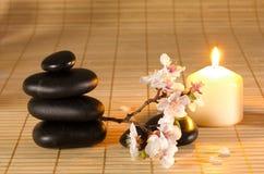 Черные камни, свечка и ветвь цветка. Стоковая Фотография RF