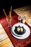 Черные каракатицы макаронных изделий покрывают краской натюрморт на деревянном столе с красными деревенскими tableclothes Пробел  стоковые фотографии rf