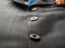 Черные кнопки на ` s человека одевают предпосылка с голубой связью , близкое поднимающее вверх Стоковое Изображение RF