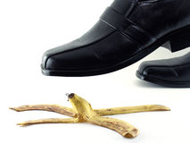 Черные кожаные ботинки топчут корку банана на белой предпосылке Стоковые Изображения
