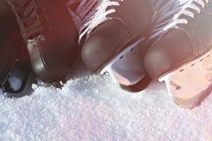 Черные коньки хоккея и для фигурное катание снег, яркое солнце стоковые фотографии rf