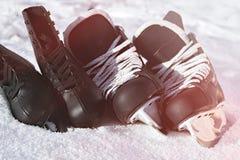 Черные коньки хоккея и для фигурное катание снег, яркое солнце стоковые фото