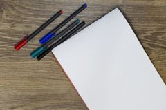 Черные, красные, зеленые и голубые отметки и белый лист бумаги на таблице стоковые изображения