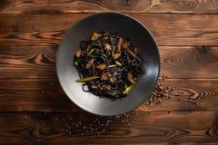 Черные лапши с мраморизованной говядиной на деревянной предпосылке стоковое изображение