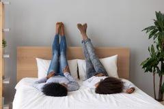 Черные мать и дочь ослабляют на говорить кровати стоковая фотография