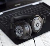 Черные наушники и портативный компьютер Стоковые Фотографии RF