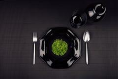 Черные лоснистые пустые плита, ложка, вилка, чашка и зеленое растение на темной striped предпосылке, взгляд сверху Стоковое Изображение RF