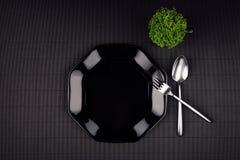 Черные лоснистые пустые плита, ложка, вилка, чашка и зеленое растение на темной striped предпосылке, взгляд сверху Стоковая Фотография RF