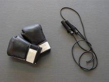 Черные перчатки бокса и веревочка скачки на циновке спортзала Стоковое фото RF