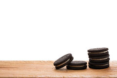 Черные печенья на деревянной доске с белой предпосылкой Стоковые Фото