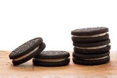 Черные печенья на деревянной доске с белой предпосылкой Стоковая Фотография