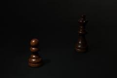 Черные пешка и ферзь на черной предпосылке стоковое фото