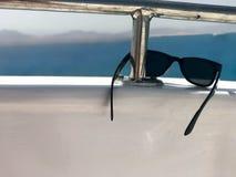 Черные пластичные солнечные очки висят на железных перилах на яхте против голубых моря и гор Стоковые Фото