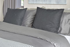 Черные подушки на кровати в серых постельных принадлежностях цветовой схемы дома Стоковые Изображения RF