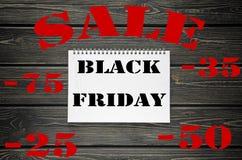 Черные продажи пятницы рекламируя плакат на черной деревянной предпосылке Стоковое Изображение