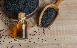 Черные семена и эфирное масло тимона с шаром и деревянными лопаткоулавливателем или ложкой стоковые изображения rf