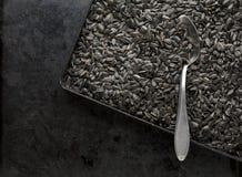 Черные семена подсолнуха в сковороде с ложкой стоковая фотография