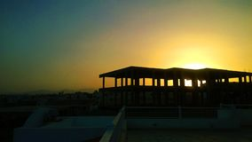 Черные силуэты крыш заходящее солнце стоковая фотография rf
