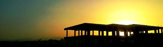 Черные силуэты крыш заходящее солнце Стоковое Изображение