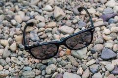 Черные стекла солнца на seashore стоковое изображение