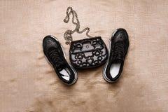 Черные тапки на белой толстой подошве украшенной с чернотой сверкнают и черная муфта со звездочками и на цепи на беже стоковые фото