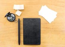 Черные тетрадь, ручка, компас и визитная карточка на деревянной таблице, насмешке Стоковое Изображение