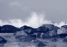 Черные утесы защищая побережье против разбивая белых волн Стоковые Фото