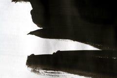 Черные ходы щетки на белой бумаге при одна изолированная рука Стоковая Фотография RF