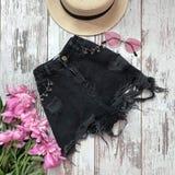 Черные шорты джинсовой ткани на деревянной предпосылке стоковое фото