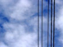Черные электрические провода на предпосылке пасмурного голубого неба стоковые фотографии rf