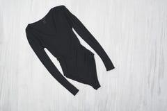 Черные bodysuits с рукавами на деревянной предпосылке модно стоковое фото rf