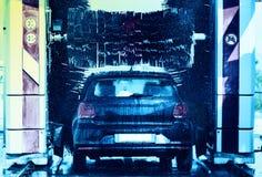 Черный автомобиль в автоматической мойке стоковые фото